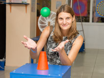Happy girl at an exhibit with a flying ball in the Museum of entertaining science Einstein. Volgograd, Russia - August 31, 2015: A girl holding hands under a Royalty Free Stock Photos