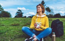 Happy girl with eyes closed holding in hands cup of hot tea on green grass in outdoors nature park, beautiful woman hipster enjoy. Drinking cup of coffee stock images