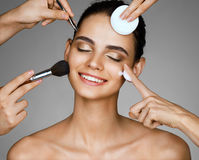 Happy girl with eyes closed surrounded by hands of makeup artists with brushes,cotton sponge and moisturizer cream near her face. Photo of beautiful woman on Stock Photos