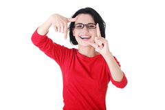Happy girl with face in frame of palms. Royalty Free Stock Image