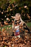 Happy girl among falling autumn leaves in park Stock Photo