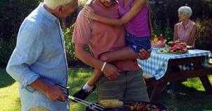 Happy girl, father and grandfather preparing barbecue 4k