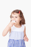 Happy girl with Feast cookies. Happy girl eating kahk el Eid ( Feast Cookies Stock Images