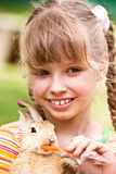Happy girl feed rabbit with carrot. Royalty Free Stock Photos