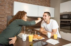 Happy girl feeding her boyfriend in a breakfast Royalty Free Stock Photography