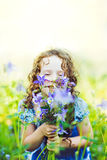 Happy girl in a field with a bouquet of wildflowers. Stock Photos