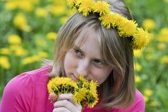 Happy girl in the field of dandelions Stock Photos