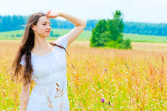 Happy girl in field with flowers Royalty Free Stock Images