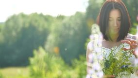 Happy girl in a field with flowers in nature. girl in a field smiling woman holding a bouquet outdoor of flowers stock footage