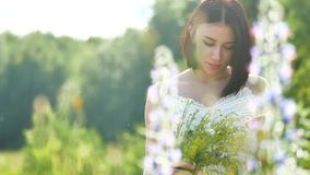 Happy girl in a field with flowers in nature. girl in a field smiling woman holding a outdoor bouquet of flowers stock video footage