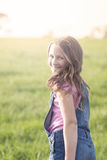 Happy girl in field, looking back to camera Stock Photography