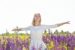 Happy girl on the field with lupines. Beautiful blonde young woman in a field with blooming lupines stock image