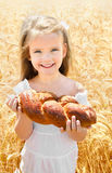 Happy girl on field of wheat. With bread Stock Photos