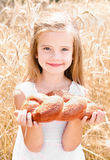 Happy girl on field of wheat with bread Royalty Free Stock Photo