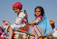 Happy girl with a fiend like a royal family drive to the Desert Festival. JAISALMER, INDIA: Happy girl with a fiend like a royal family sitting on the camel back Royalty Free Stock Image