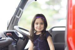 Happy Girl in Firefighter Car Stock Photo