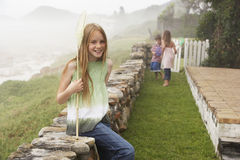 Happy Girl With Fishing Net Sitting On Stone Wall At Yard Royalty Free Stock Photo