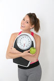Happy girl fitness outfit holding scale and green apple Royalty Free Stock Photo