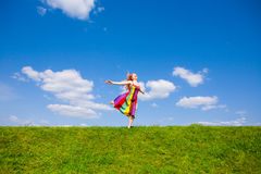Happy girl fleeing on a meadow. Against the backdrop of blue sky Royalty Free Stock Images
