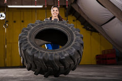 Happy girl flipping a tire Stock Photo