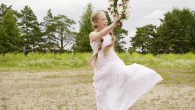 Happy girl with floral wreath. Adorable happy child in white dress holding beautiful wreath with flowers, running and jumping on meadow with trees and flowers stock video footage