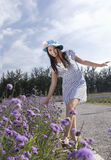 A happy girl and flower. A happy girl is walking along and watching flower Royalty Free Stock Photos