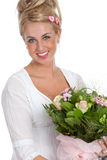Happy girl with flowers. Beautiful young girl with a bunch of pink flowers smiling Stock Image