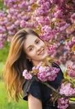 Happy girl in the flowers of sakura Stock Image