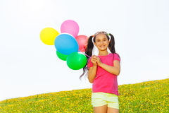 Happy girl with flying balloons in the air Stock Image