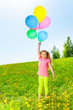 Happy girl with flying balloons stands on grass Royalty Free Stock Image