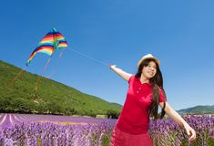 Happy girl flying colorful kite in lavender field Stock Photography