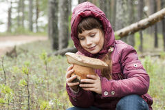 Happy girl in a forest sees large mushroom . Stock Images