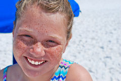 Happy girl with freckles at the beach. Close up of smiling teen girl in the sand on vacation Stock Images