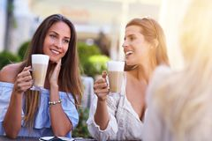 Happy girl friends in cafe during summer time Royalty Free Stock Images