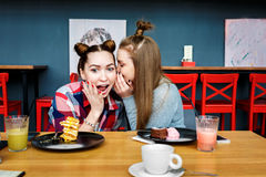 Happy girl friends have cup of coffee in modern city restaurant Stock Photography