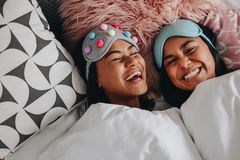 Happy girl friends laughing lying on bed royalty free stock image