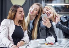 Happy girl friends. Laughing girl friends sitting in a cafes and using smartphone, breakfast. Ladies drinking coffee Royalty Free Stock Image