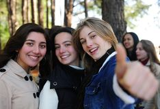 Happy girl with friends showing thumbs up sign. Group of teenage girls on vacation during a trip in the forest stock images