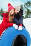 Happy girl friends with snow tubes outdoors Stock Image