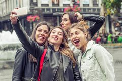 Happy girl friends taking selfie photos in the street stock photography
