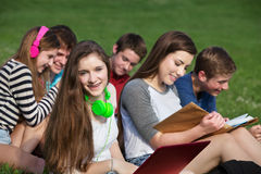 Happy Girl with Friends. Happy teen girl with friends studying outdoors Royalty Free Stock Photography