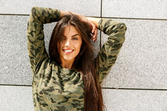 Happy girl in front of stone wall Royalty Free Stock Image