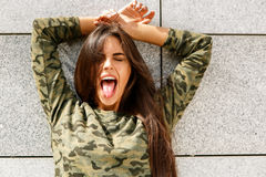 Happy girl in front of stone wall Stock Images