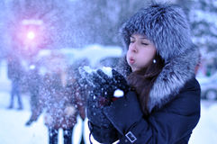 Happy girl with fur cap and gloves blowing snowflakes in the winter city.  Royalty Free Stock Photo