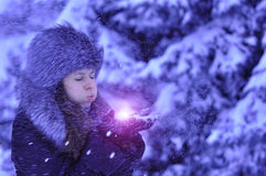 Happy girl with fur cap and gloves blowing snowflakes in the winter city.  Royalty Free Stock Images