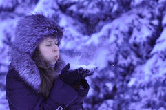 Happy girl with fur cap and gloves blowing snowflakes in the winter city.  Royalty Free Stock Photos