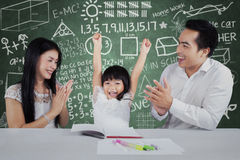 Happy girl get applaud in classroom. Cheerful little girl get appreciation and applause from her parents after studying Stock Images