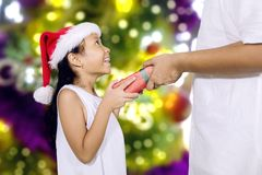 Happy girl gets a Christmas gift from her father royalty free stock photo