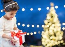 Happy girl with gift box over christmas lights Stock Photo