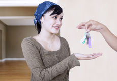 Happy girl given house key - indoor. Happy girl given house key by unrecognizable person royalty free stock photo